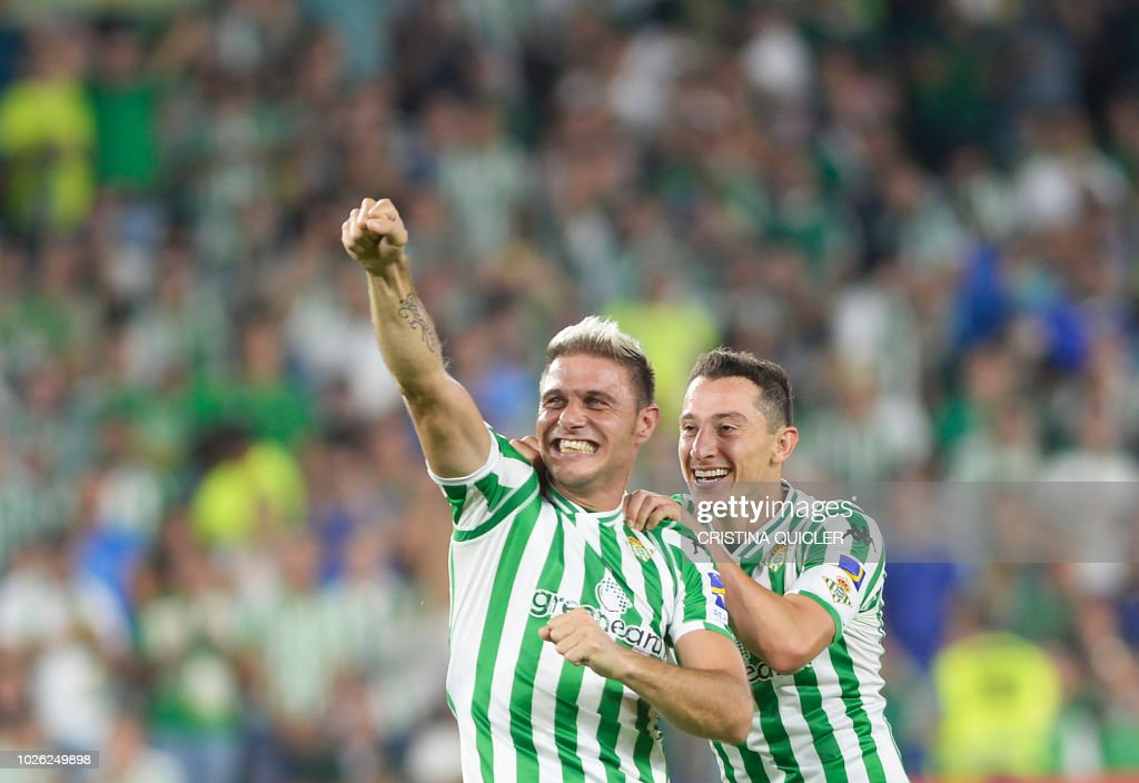 Real Betis' Spanish midfielder Joaquin (L) celebrates with Real Betis' Mexican midfielder Andres Guardado at the end of the Spanish league football match between Real Betis and Sevilla FC at the Benito Villamarin stadium in Seville on September 2, 2018.