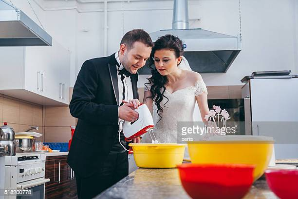 Real bride and groom baking wedding cake in kitchen