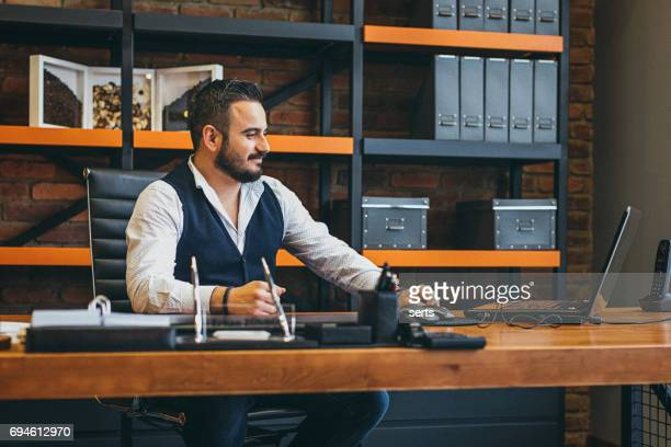 Real businessman sitting and working at desk in office