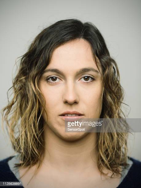 real caucasian young woman with blank expression looking at camera - police mugshot stock pictures, royalty-free photos & images