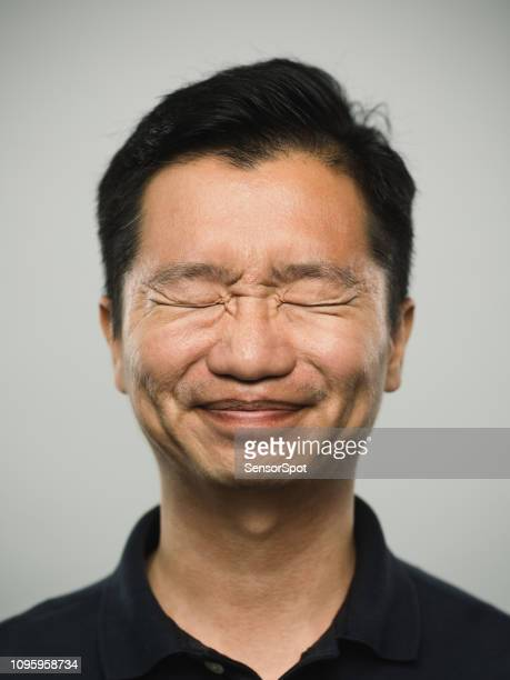 real chinese man with grimacing expression and eyes closed - ugly face stock pictures, royalty-free photos & images