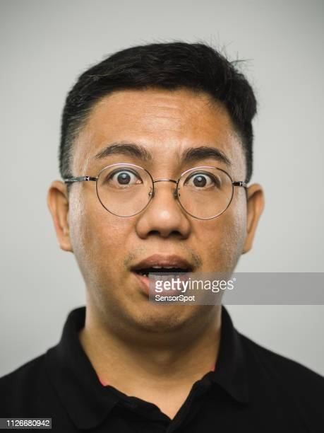 驚いた表情で本物の中国男 - サプライズ ストックフォトと画像