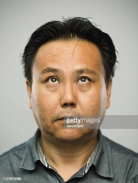 Real chinese mature man with blank expression looking up