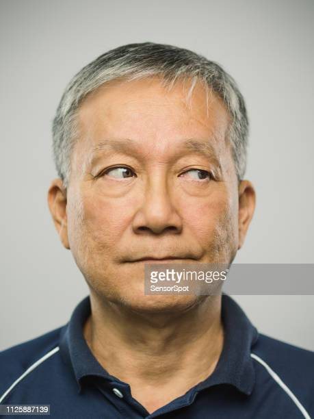 Real chinese senior man with blank expression looking to the side