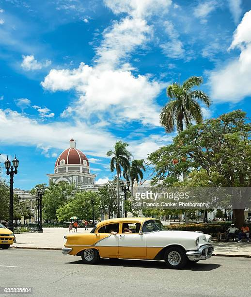 Real Cuban culture city life a taxi and Town Hall in Cienfuegos, Cuba, a UNESCO heritage site