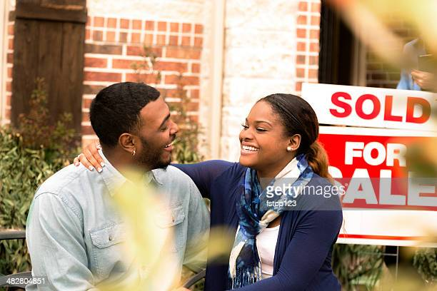 Real Estate: African descent couple buys first home. Sign background.
