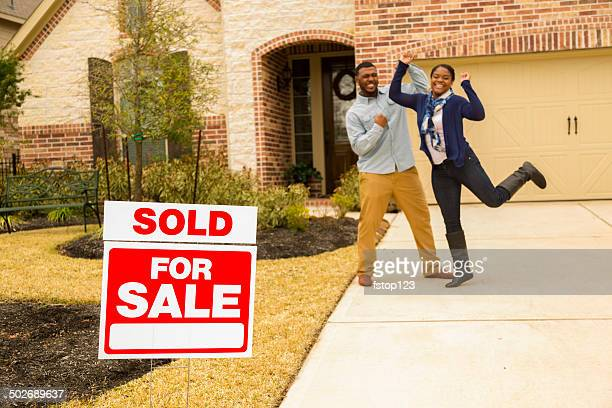 real estate: african descent couple jumps for joy. happy homeowners! - real estate sign stock pictures, royalty-free photos & images