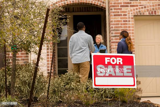 Real Estate: African descent couple meets with realtor. Buying home.