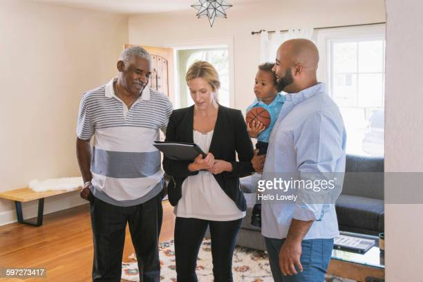Real estate agent and clients using digital tablet