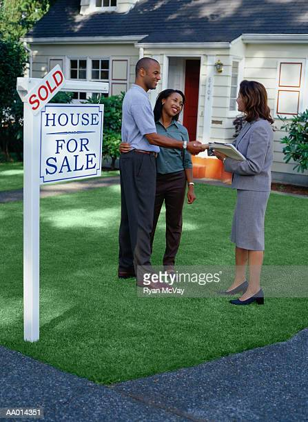 real estate agent and couple standing in front of sold house - real estate sign stock pictures, royalty-free photos & images