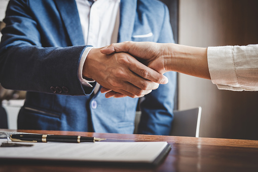 Real estate agent and customers shaking hands together celebrating finished contract after about home insurance and investment loan, handshake and successful deal 1026040262