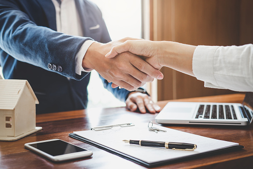 Real estate agent and customers shaking hands together celebrating finished contract after about home insurance and investment loan, handshake and successful deal 1026040678