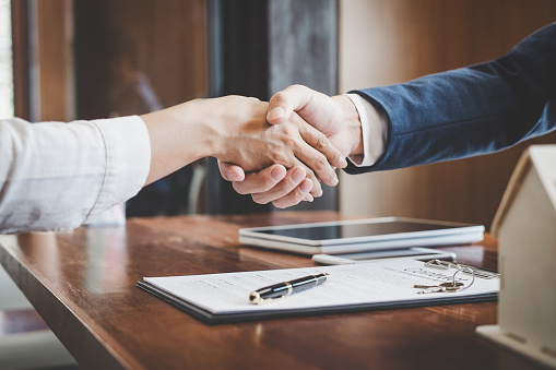Real estate agent and customers shaking hands together celebrating finished contract after about home insurance and investment loan, handshake and successful deal 1069232832