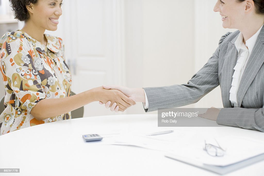 Real estate agent and woman shaking hands : Stock Photo