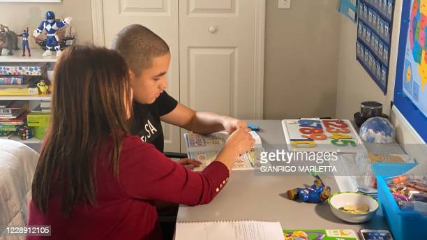 Real estate agent Aracelis Bonet home schools her son Adam Martinez who is affected by severe autism, in their Orlando home on October 1, 2020. - As...
