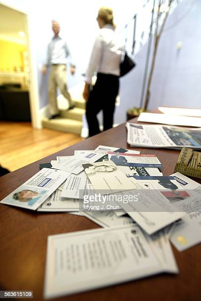 Real estate agent business cards are collected on a table at an open house in Sherman Oaks on Caravan Day The day is for realtors to preview new...