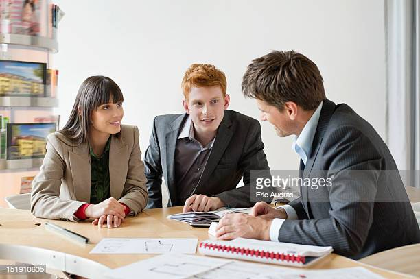 Real estate agent discussing property documents to his clients