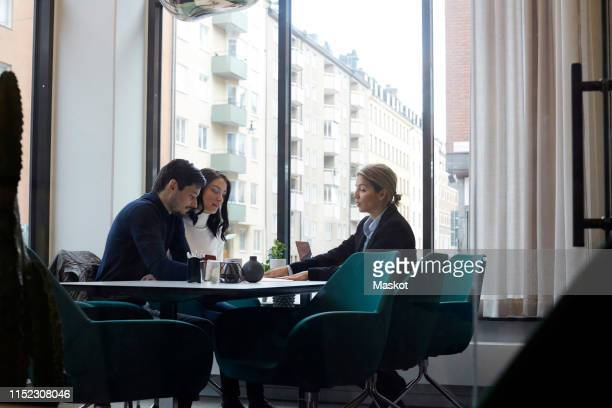 real estate agent discussing with couple in office - bens imóveis imagens e fotografias de stock
