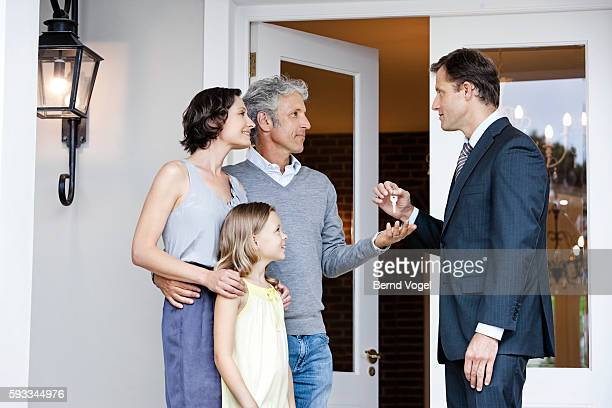Real estate agent giving a family keys to their new house