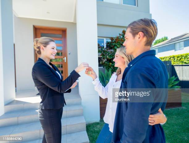 real estate agent giving a young couple the key to their new house. - real estate stock pictures, royalty-free photos & images