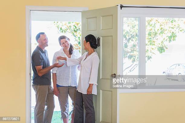 Real estate agent giving couple keys to new home