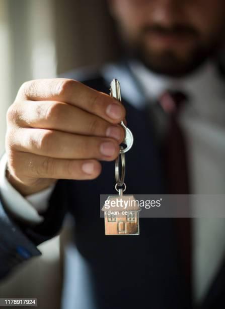 家の鍵を与える不動産業者 - 賃貸借 ストックフォトと画像