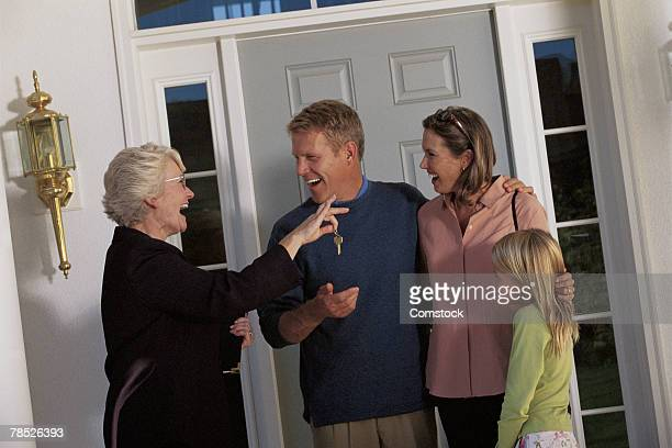 Real estate agent giving keys to family