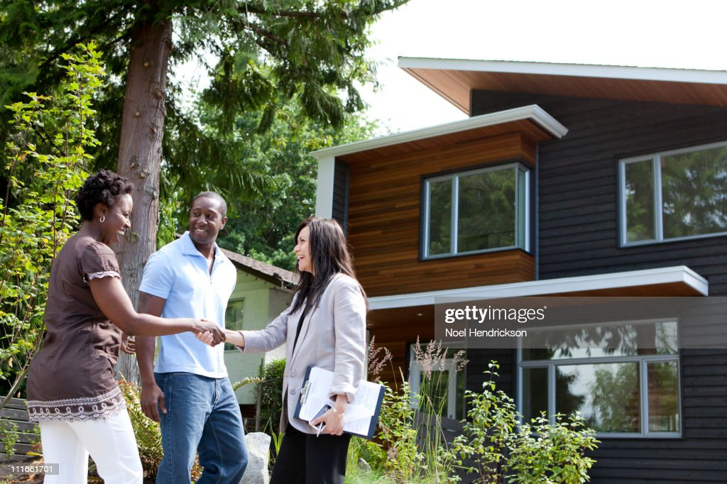 Real estate agent greeting couple at house : Stock Photo