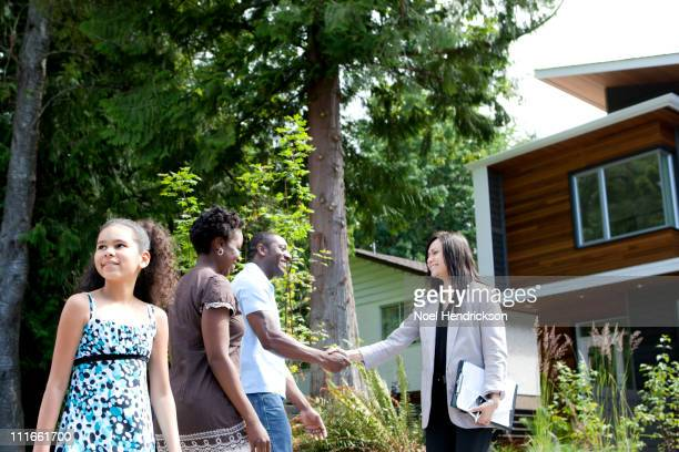 Real estate agent greeting family at house