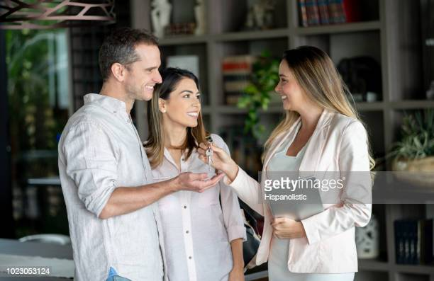 real estate agent handing the keys to customers at their new home while she holds a tablet - real estate broker stock photos and pictures