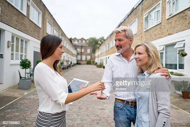 Real estate agent handling keys to a couple