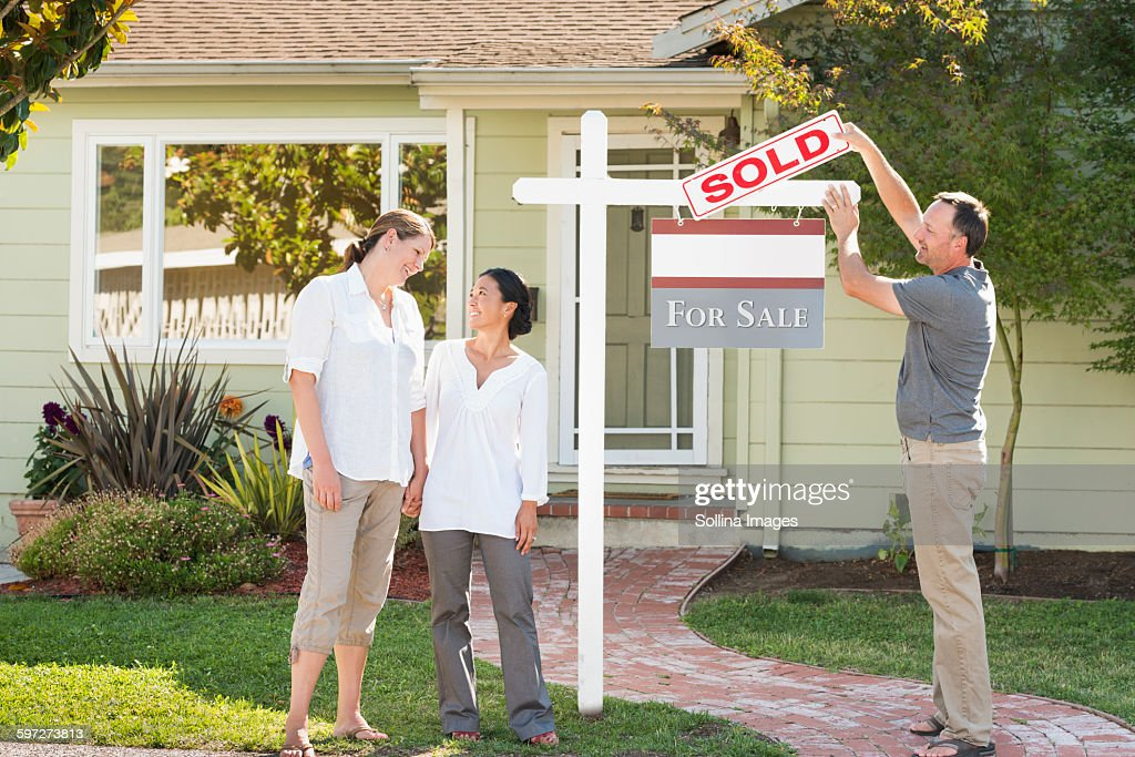 Real estate agent hanging sign outside house : Stock Photo
