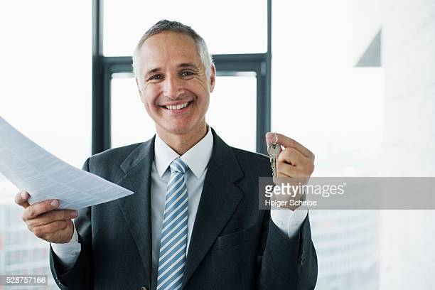 Real estate agent holding keys and deed