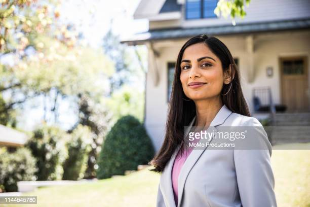 real estate agent in front of home - femme indienne photos et images de collection