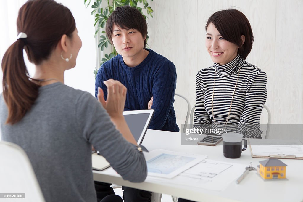 Real estate agent is description to couple about  new house : Stock Photo
