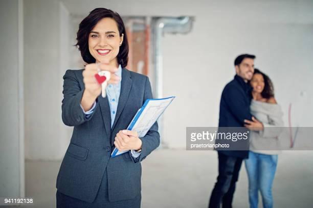agente imobiliário está segurando a chave para um novo apartamento - corretor de imóveis - fotografias e filmes do acervo