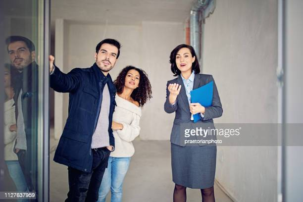 real estate agent is showing balcony/terrace of new apartment to a couple - real estate stock pictures, royalty-free photos & images