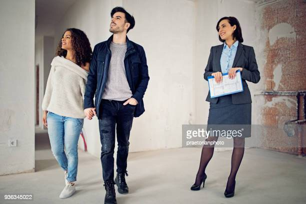 real estate agent is showing new apartment to a young couple - traders stock pictures, royalty-free photos & images