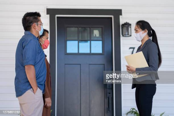 real estate agent meeting with clients in masks - real estate agent stock pictures, royalty-free photos & images
