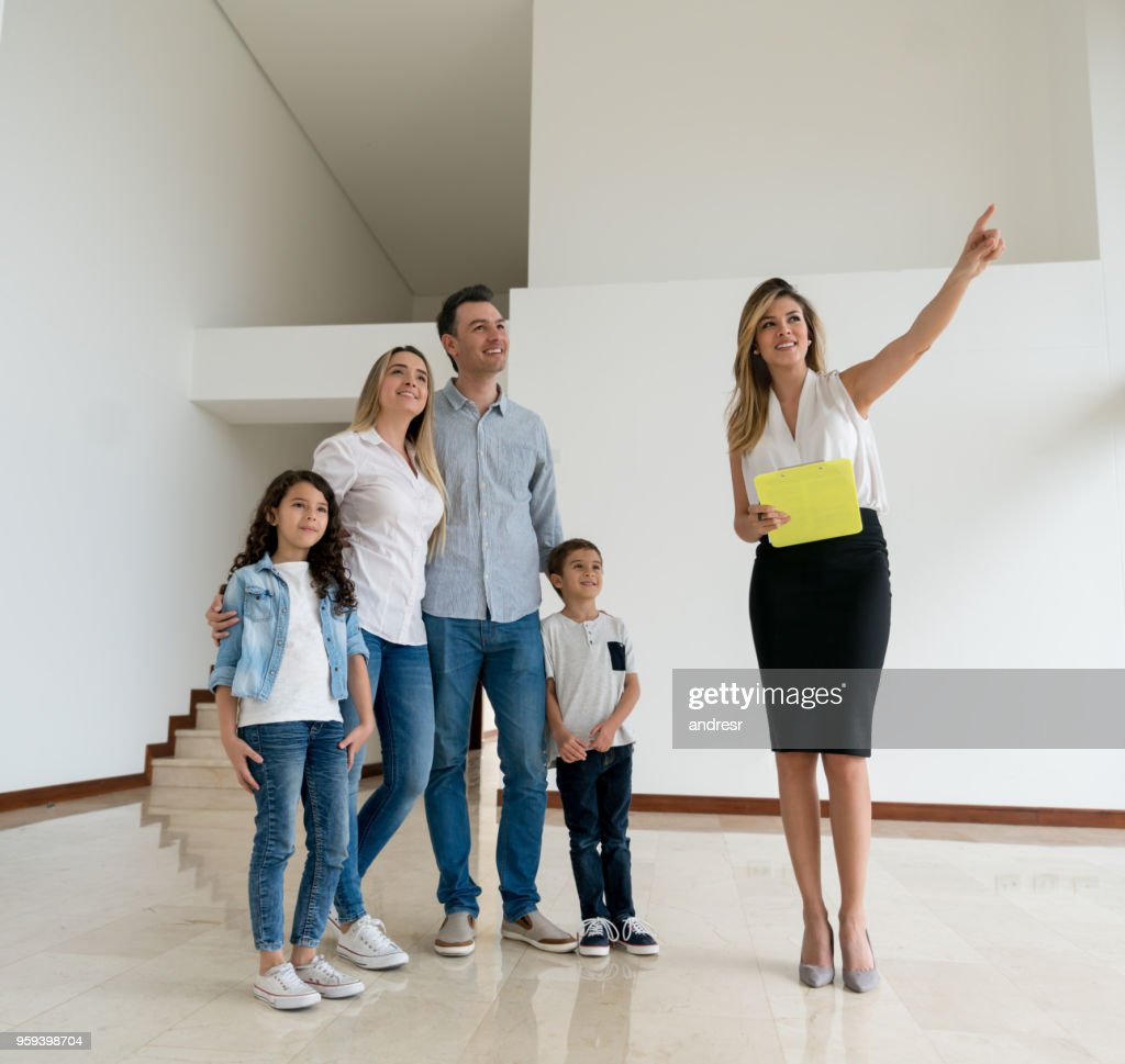 Real estate agent showing a house to a family : Stock Photo
