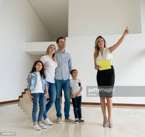 real estate agent showing a house to a family - real estate broker stock photos and pictures