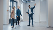 Real Estate Agent Showing a New Empty Office Space to Young Male and Female Hipsters. Entrepreneurs Meet the Broker with a Tablet and Discuss the Facility They Wish to Purchase or Rent.