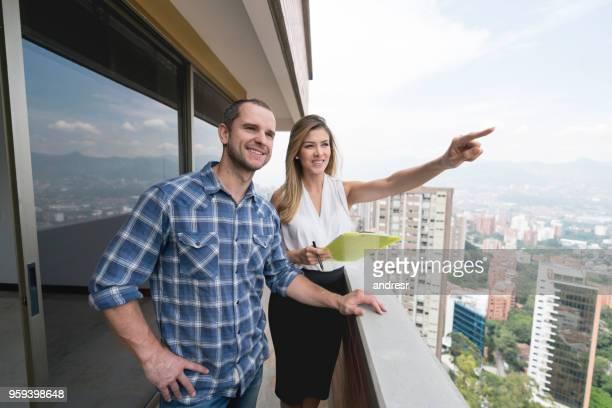 agente imobiliário mostrando uma propriedade de um homem feliz - corretor de imóveis - fotografias e filmes do acervo