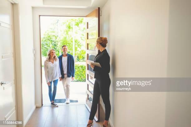 agente inmobiliario mostrando a una joven pareja una nueva casa. - agente inmobiliario fotografías e imágenes de stock