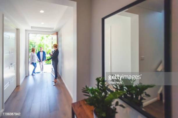real estate agent showing a young couple a new house. - real estate stock pictures, royalty-free photos & images