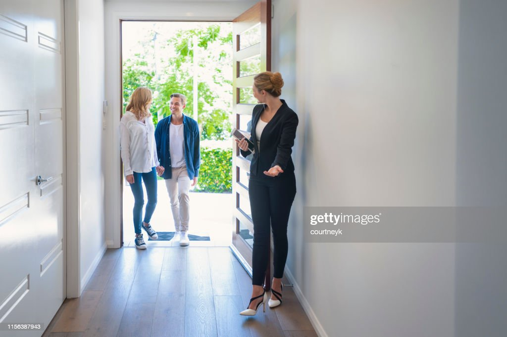 Real estate agent showing a young couple a new house. : Stock Photo