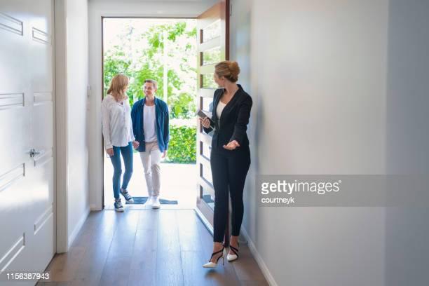 real estate agent showing a young couple a new house. - bens imóveis imagens e fotografias de stock
