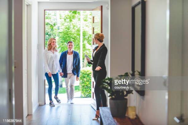 real estate agent showing a young couple a new house. - real estate agent stock pictures, royalty-free photos & images