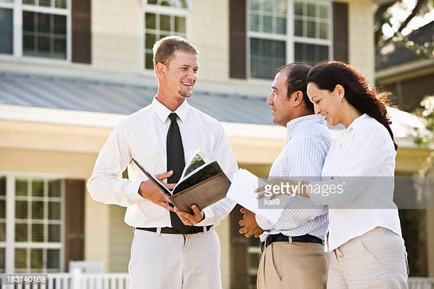 Real estate agent showing brochure of house to Hispanic couple
