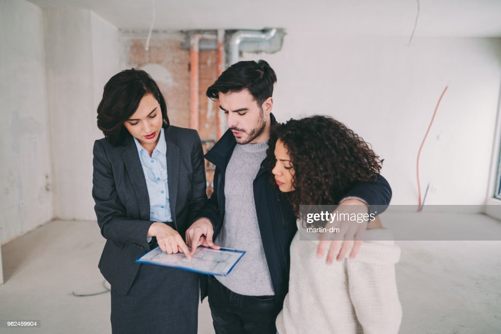 Real estate agent showing condo for sale to young couple : Stock Photo